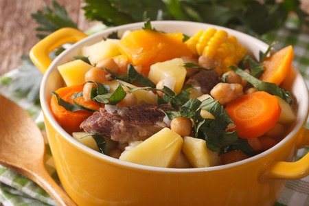 andalusian cuisine: South American cuisine: Puchero soup with chickpeas close-up in a pot on the table. horizontal Stock Photo