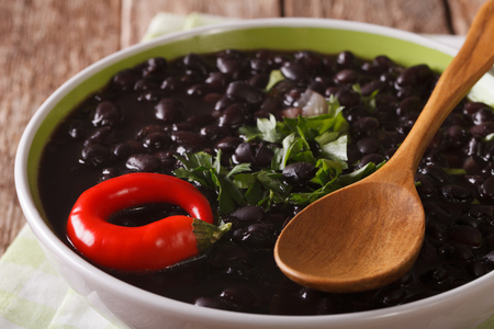 Stewed spicy black beans close up in a bowl on the table. Horizontal Standard-Bild