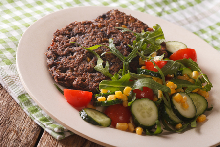 Vegetarian black bean burgers and fresh vegetable salad close-up on a plate on the table.  Horizontal