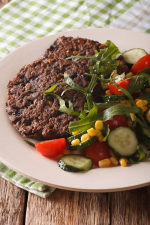 Vegetarian black bean burgers and a salad of fresh vegetables close-up on a plate on the table. vertical