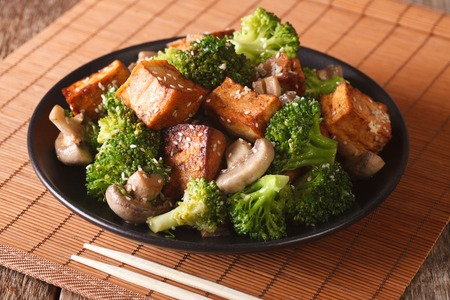 Fried tofu cheese with broccoli, mushrooms and teriyaki sauce close-up on a plate. horizontal Stock Photo