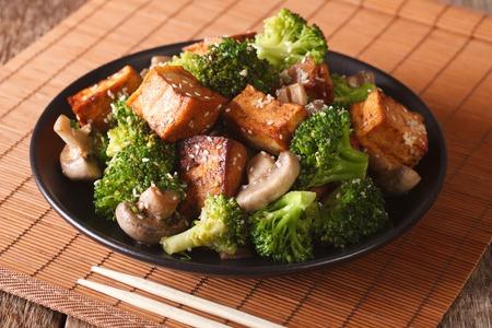 Gebakken tofu-kaas met broccoli, champignons en teriyaki-sausclose-up op een plaat. horizontaal