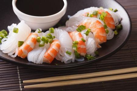 Shirataki-Nudeln mit Garnele, Frühlingszwiebeln und Sojasoße auf einer Plattennahaufnahme. horizontal Standard-Bild