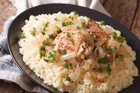 Yassa chicken stewed with marinated onions and couscous close up on a plate. horizontal