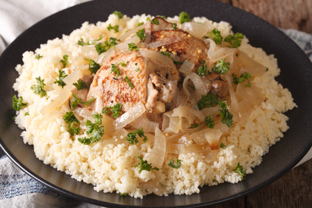 West African food: Chicken Yassa and couscous with onions on a plate macro. horizontal Stock Photo