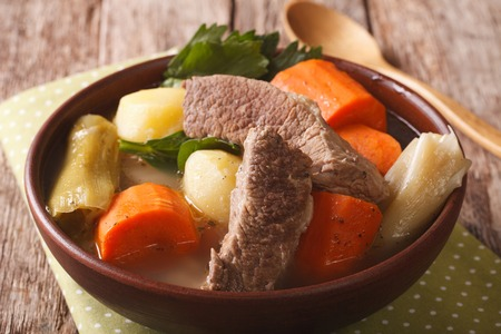 Homemade hot beef soup with vegetables close up in a bowl on the table. horizontal
