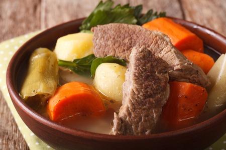 냄비 -au-feu 테이블에 그릇 매크로에서 야채와 함께 쇠고기 수프. 수평의