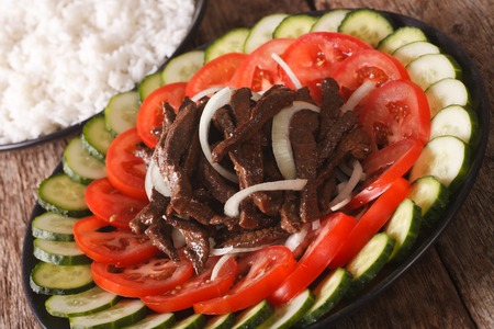 Cambodian food: beef Lok Lak with fresh vegetables and a side dish of rice close-up on the table. Horizontal Stock Photo