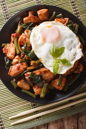 Stir-Fry Chicken with basil, green beans and a fried egg on a plate close-up. vertical view from above