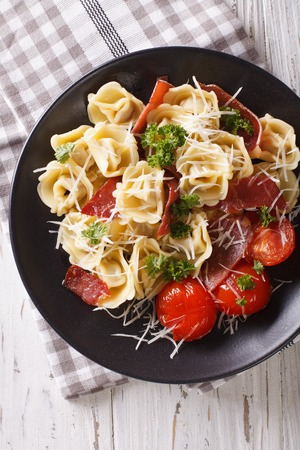 Italian tortellini with prosciutto, tomatoes and parmesan close-up on a plate. vertical view from above