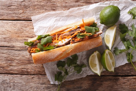 Vietnamese sandwich with cilantro and carrot close-up on the table. horizontal view from above Stock Photo - 64385123