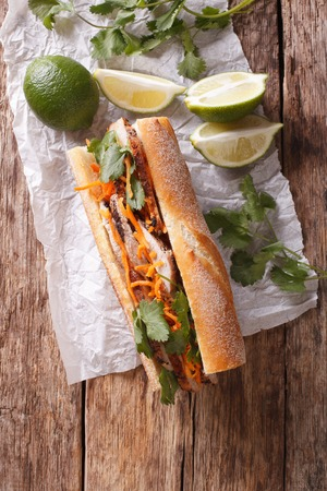 Vietnamese sandwich with cilantro and carrot close-up on the table. vertical view from above Stock Photo