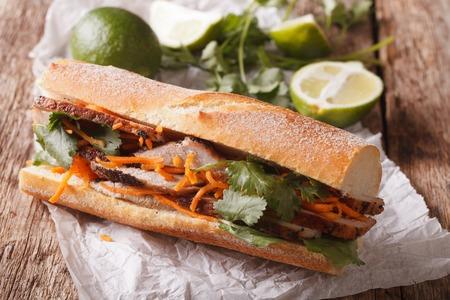 실란트와 테이블에 당근 근접 베트남어 돼지 고기 반미 샌드위치. 수평