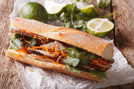 Vietnamese Pork Banh Mi Sandwich with Cilantro and carrot close-up on the table. Horizontal