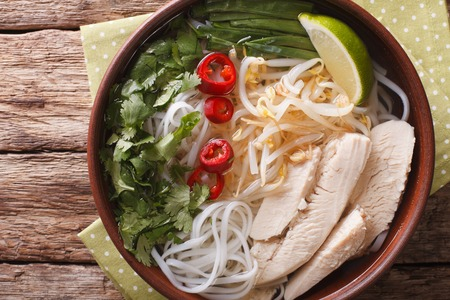 Vietnamese soup Pho Ga with chicken and rice noodles in a bowl close-up. horizontal view from above