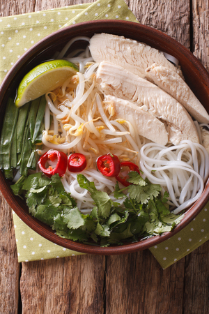Vietnamese soup Pho Ga with chicken and rice noodles in a bowl close-up. vertical view from above Stock Photo