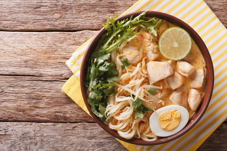 닭고기, 계란, 국수와 허브와 함께 말레이시아 laksa 수프 테이블에 그릇에 닫습니다. 위에서 가로보기