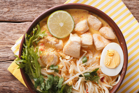 Malaysian laksa soup with chicken close up in a bowl on the table. horizontal view from above