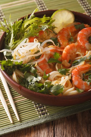 Asian food: soup with shrimps, noodles and herbs close up in a bowl on the table. vertical