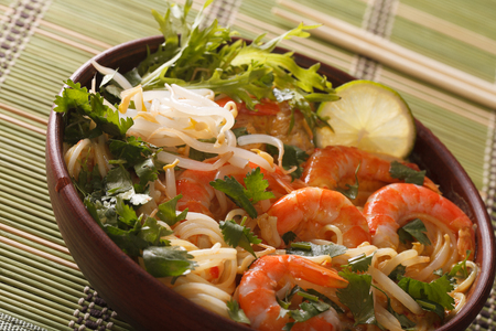 Thick soup with shrimps, noodles and herbs close up in a bowl on the table. horizontal Stock Photo