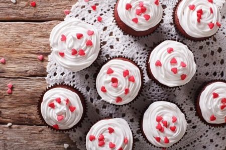 red velvet cupcake: red velvet cupcakes decorated with hearts close-up on the table. horizontal view from above