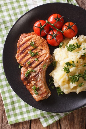 Grilled pork steak with mashed potatoes on a plate close-up. vertical view from above