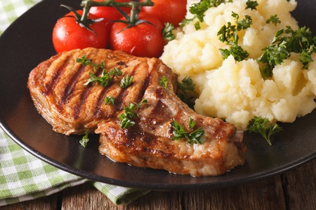 Grilled pork steak with mashed potatoes on a plate close-up. Horizontal