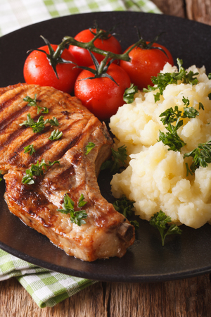 Grilled pork chop with mashed potatoes on a plate close-up. vertical Stock Photo