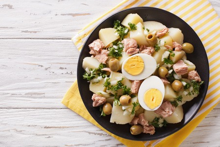 Spanish salad Patatas Alinadas of boiled potatoes with tuna, egg and olives close-up on a plate. horizontal view from above