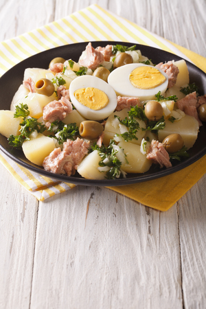 Spanish cuisine: Patatas Alinadas - Potatoes with Dressing closeup on a plate. Vertical