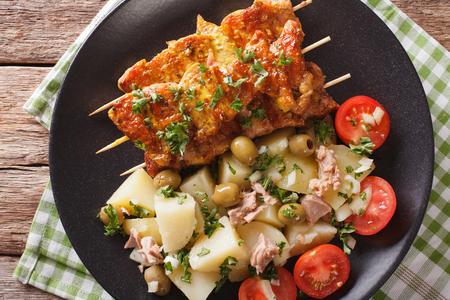 Spanish kebab Pinchos Morunos and salad Patatas Alinadas close-up on a plate. horizontal view from above Foto de archivo