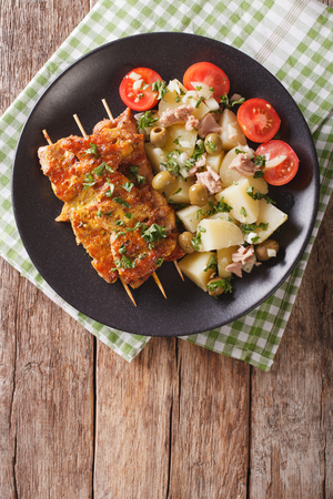 Spanish Pork Kabobs - Pinchos Morunos and Easy Potatoes with Dressing - Patatas Alinadas closeup on a plate. vertical view from above
