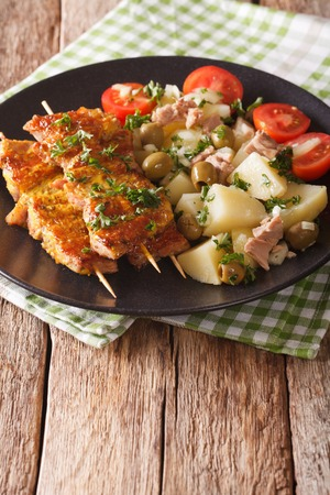 Spanish Food: kebab Pinchos Morunos and vegetables salad close-up on a plate on the table. vertical