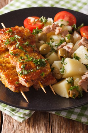 Spanish kebab Pinchos Morunos and potato salad with tuna and herbs closeup on a plate. Vertical