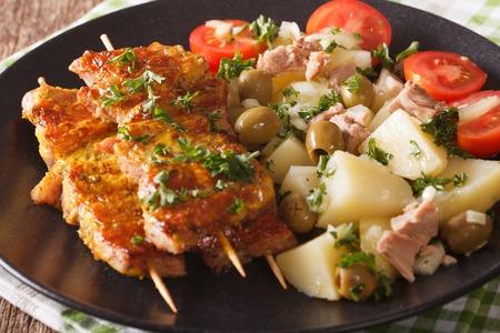 Spanish kebab Pinchos Morunos and potato salad with tuna and herbs closeup on a plate. horizontal