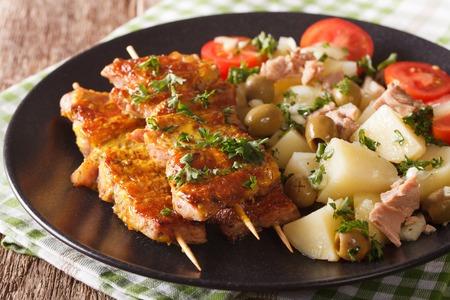 Spanish skewers Pinchos Morunos and potato salad with tuna on the plate closeup. horizontal