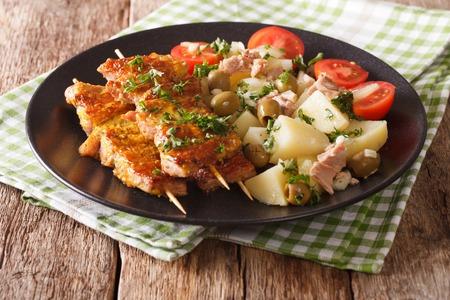 Spanish kebab Pinchos Morunos and salad Patatas Alinadas close-up on a plate. Horizontal