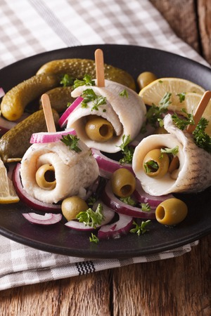 rolls of herring with olives, onions, pickles and lemon close-up on a plate. vertical