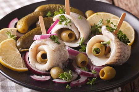 rollmops herring with olives, onions, pickles and lemon close-up on a plate. horizontal Stock Photo