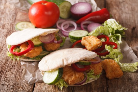 nappa: Tasty pita with chicken nuggets, cucumber, nappa cabbage, onion and bell peppers closeup on the table. horizontal Stock Photo