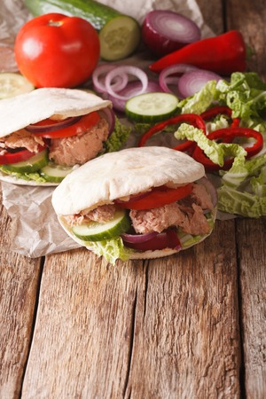 nappa: Healthy sandwich: pita with tuna, cucumber, nappa cabbage, onions, peppers and tomatoes close-up on the table. vertical Stock Photo