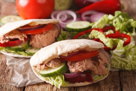 nappa: Tasty pita with tuna, cucumber, nappa cabbage, onion and tomatoes closeup on the table. Horizontal Stock Photo