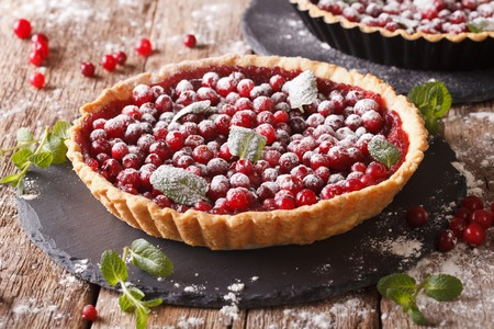 cranberry tart with jam, powdered sugar decorated with mint close up on the table. horizontal Stock Photo