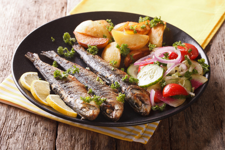 Fried sardines with roasted potatoes and fresh salad on the plate closeup. horizontal
