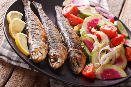 Mediterranean cuisine: grilled sardines with fresh vegetable salad close-up on a plate. horizontal  Stock Photo