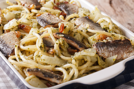 Italian pasta with sardines, fennel, raisins and pine nuts macro in a baking dish. horizontal Stock Photo