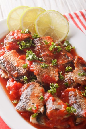 sardine can: Tasty sardines in tomato sauce with lime and parsley close-up on a plate. vertical