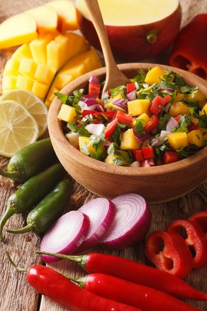 Mexican salsa with mango, pepper, jalapeno, cilantro and onions in a bowl close-up. vertical