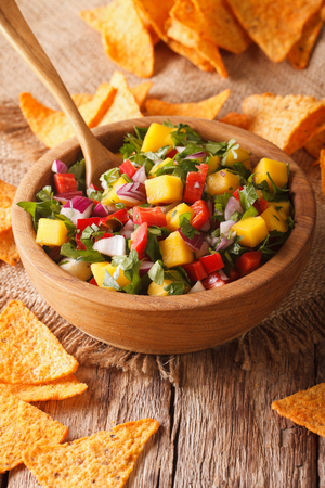 Mexican Food: salsa with mangoes, peppers, cilantro and onion close up in a bowl and nachos on the table. vertical Stock Photo