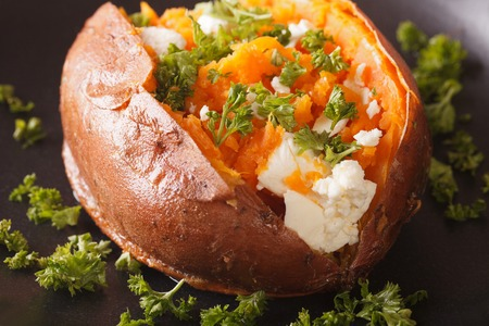 Delicious baked sweet potatoes stuffed with feta cheese and parsley close-up on a black plate. Horizontal